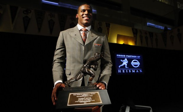 Auburn Tigers quarterback Cam Newton poses with the 2010 Heisman Trophy