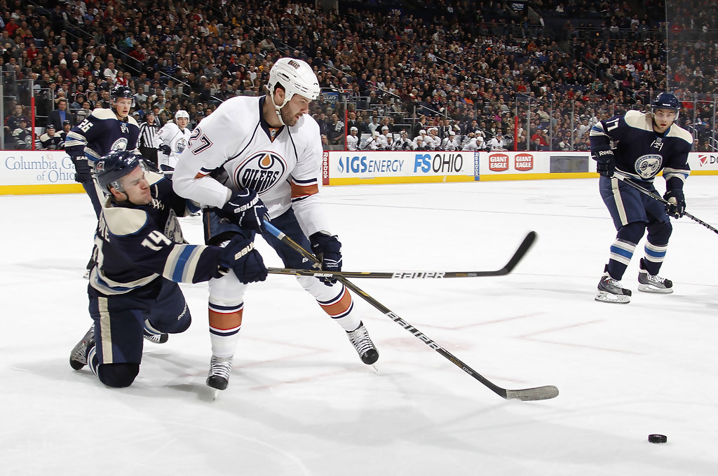 Edmonton Oilers forward Dustin Penner tries to control the puck while Grant Clitsome looks against the Columbus Blue Jackets