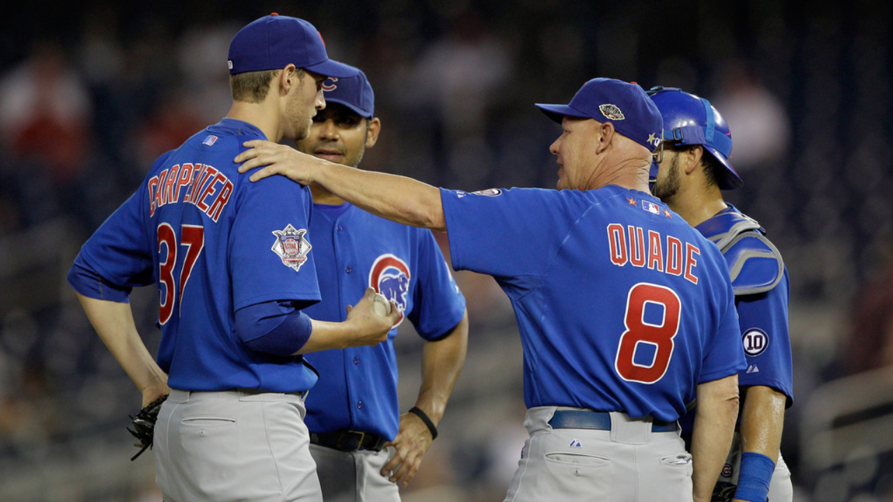 Chicago Cubs pitcher Chris Carpenter talks with manager Mike Quade after a pitching change against the Washington Nationals