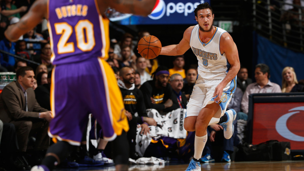 Denver Nuggets forward Danilo Gallinari dribbles the ball up the court, as Dwight Buycks defends him against the Los Angeles Lakers