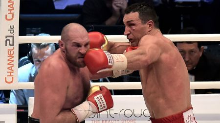 Boxer Wladimir Klitschko punches Tyson Fury in the mouth