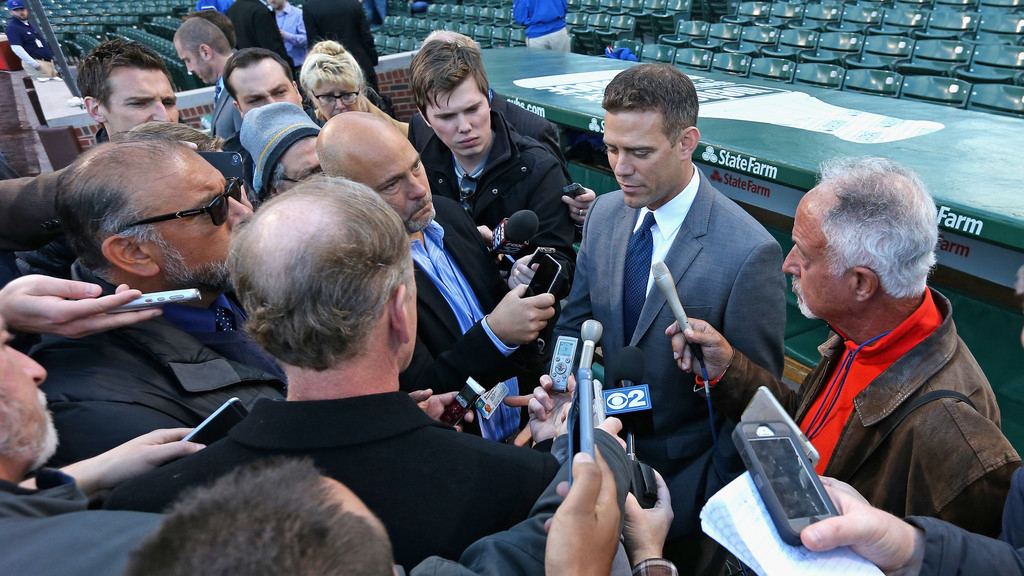 Chicago Cubs President of Baseball Operations Theo Epstein talks with reporters during batting practice before his team takes on the Cincinnati Reds