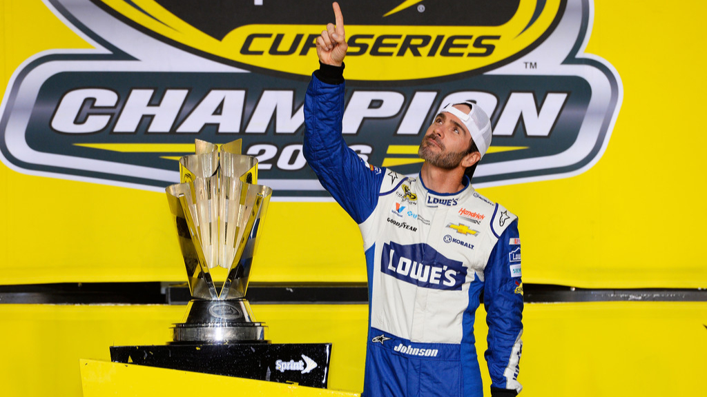NASCAR driver Jimmie Johnson points to the sky after winning the NASCAR Sprint Cup Series Championship in Victory Lane after winning the NASCAR Cup Series Ford EcoBoost 400 and the 2016 NASCAR Sprint Cup Championship