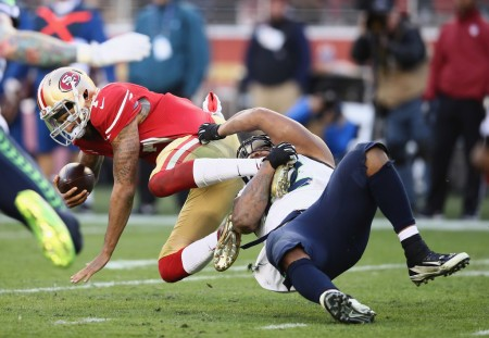 Colin Kaepernick being tackled by a Seattle Seahawks player (Getty Images)