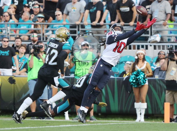 Houston Texans wide receiver DeAndre Hopkins reaches to catch the football as Jacksonville Jaguars defensive backs Jalen Ramsey and Barry Church look on (Getty Images)