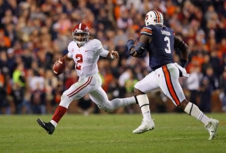 Alabama Crimson Tide quarterback Jalen Hurts trying to escape an Auburn Tigers defender (Getty Images)