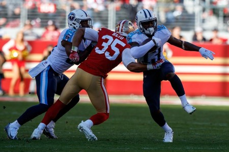 Former San Francisco 49ers safety Eric Reid attempts to tackle Tennessee Titans player Taywan Taylor