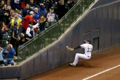 Christian Yelich sliding into the bottom frame of the Miller Park outfield (Getty Images)