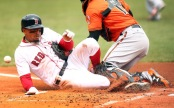 Mookie Betts is seen here sliding into home plate, colliding with Baltimore Orioles catcher Chance Sisco (Getty Images)