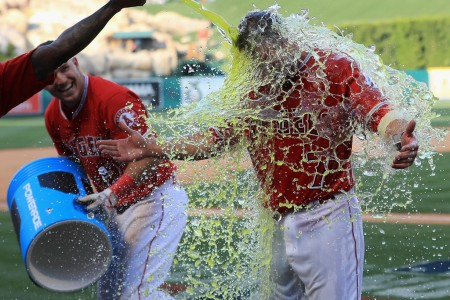 Following his game-winning home run in the 13th inning, Zach Cozart has a sports drink dumped on him by his teammate Mike Trout (Getty Images)