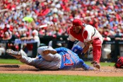 Chicago Cubs base runner Addison Russell scores a run, as St. Louis Cardinals catcher Yadier Molina attempted to block him (Getty Images)