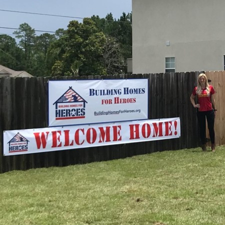 Courtney Force standing next to the fence with the Building Homes for Heroes signage (Photo by Courtney Force)