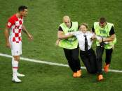 Stewards apprehend a pitch invader as Croatia's Dejan Lovren reacts (REUTERS)