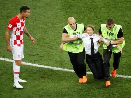 Stewards apprehend a pitch invader as Croatia's Dejan Lovren reacts (REUTERS)