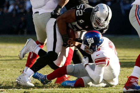 Oakland Raiders star defensive player Khalil Mack tackles New York Giants quarterback Geno Smith