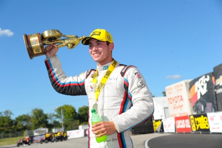 Pro Stock driver Tanner Gray holding the AAA Insurance NHRA Midwest Nationals Wally