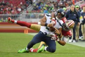 Former San Francisco 49ers safety Eric Reid tackling Seattle Seahawks quarterback Russell Wilson