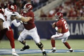 Alabama Crimson Tide quarterback Jalen Hurts looks to make a play, as Louisville defenders close in