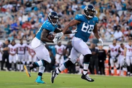 Jacksonville Jaguars running back Leonard Fournette rushing the ball, as Austin Seferian-Jenkins gets ready to block