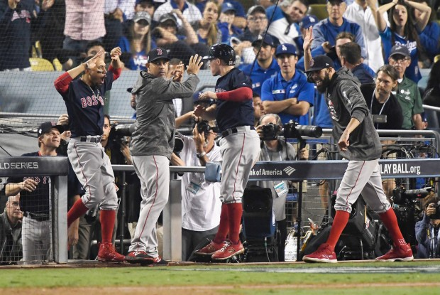 Boston Red Sox manager Alex Cora celebrating with Brock Holt after he scores a run in Game 3 of the World Series