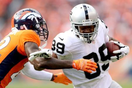 Oakland Raiders wide receiver Amari Cooper is being tackled after a reception by Denver Broncos' Tramaine Brock