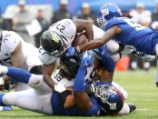 New York Giants defensive tackle Damon Harrison and linebacker Ray-Ray Armstrong tackle Jacksonville Jaguars running back Leonard Fournette