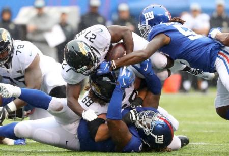 New York Giants defensive tackle Damon Harrison and linebacker Ray-Ray Armstrong tackle Jacksonville Jaguars running back Leonard Fournette