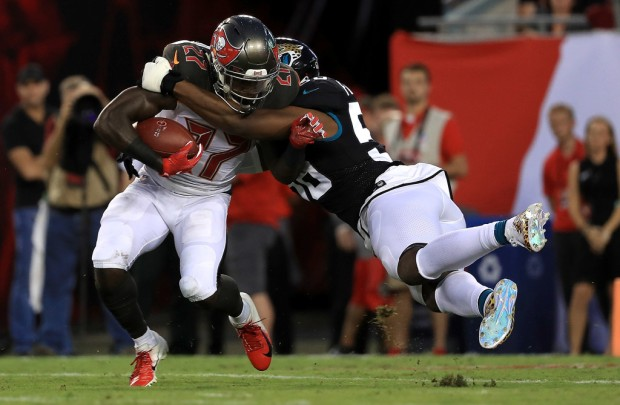Former Jacksonville Jaguars defensive end Dante Fowler tackles De'Vante Harris against the Tampa Bay Buccaneers