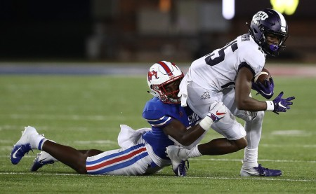 TCU Horned Frogs wide receiver and kick returner KaVontae Turpin is being tackled by SMU Mustang's Christian Davis following a reception
