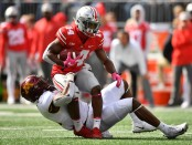 Ohio State Buckeyes wide receiver K.J. Hill is getting dragged down by Minnesota Golden Gophers' Kamal Martin
