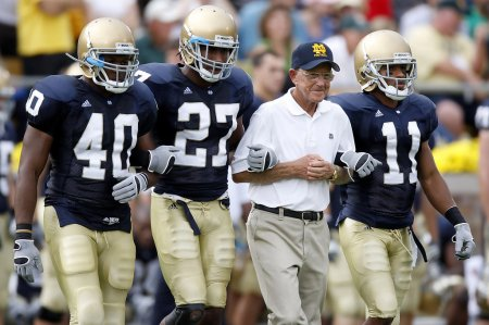 Former Notre Dame Fighting Irish head coach Lou Holtz walks out to the coin toss against the Michigan Wolverines with David Grimes, David Bruton, and Maurice Crum