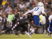 Tulsa Golden Hurricane quarterback Luke Skipper being sacked by Temple Owls' Ryquell Armstead