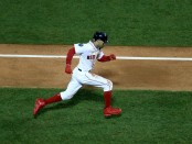 Boston Red Sox outfielder Mookie Betts scores a run against the Los Angeles Dodgers in the first inning