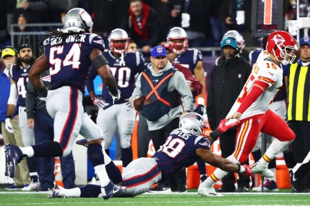 Kansas City Chiefs quarterback Patrick Mahomes II trying to escape a tackle from New England Patriots' Trey Flowers