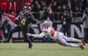 Purdue Boilermakers wide receiver Rondale Moore runs the ball and attempts to fight off Ohio State Buckeyes' Jahsen Wint