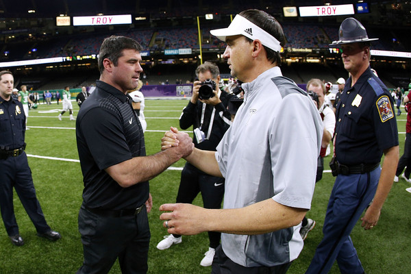 North Texas Mean Green head coach Seth Littrell shaking heads with Troy Trojans head coach Neal Brown after the R+L Carriers New Orleans Bowl