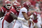 Alabama Crimson Tide quarterback Tua Tagovailoa being tackled by Arkansas Razorbacks' De'Jon Harris