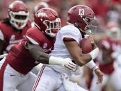 Alabama Crimson Tide quarterback Tua Tagovailoa being tackled by Arkansas Razorbacks' De'Jon Harris
