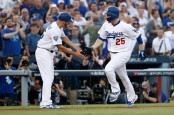 Former Los Angeles Dodgers third base coach Chris Woodward celebrates David Freese's home run during the World Series