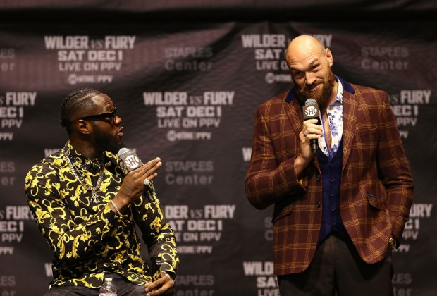 Professional boxers Deontay Wilder and Tyson Fury talking on stage during a press conference to promote their fight
