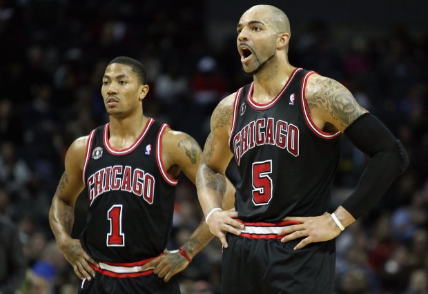 Chicago Bulls teammates Tony Parker standing next to Carlos Boozer as they look on against the Charlotte Bobcats