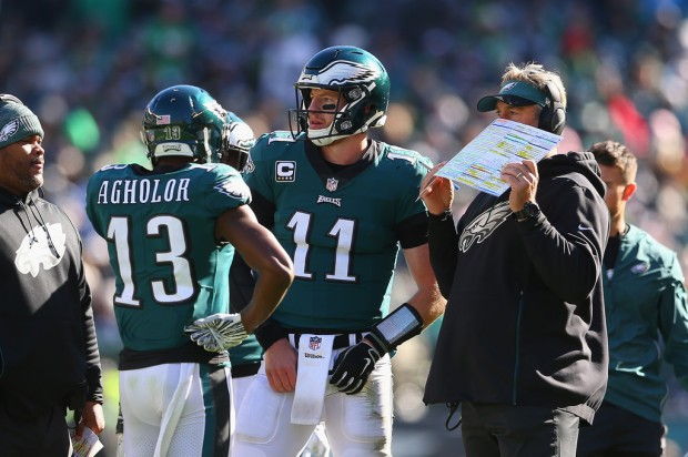 Philadelphia Eagles head coach Doug Pedersen talking to Carson Wentz and Nelson Agholor against the Carolina Panthers