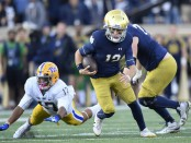 Notre Dame Fighting Irish quarterback Ian Book scrambles with the ball to avoid a tackle against the Pittsburgh Panthers by Rashad Weaver