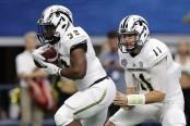 Former Western Michigan quarterback Zach Terrell hands the ball off to running back Jamauri Bogan in the Goodyear Cotton Bowl Classic
