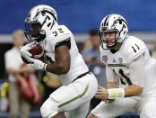 Former Western Michigan quarterback Zach Terrell hands the ball off to running back Jamauri Bogan in the Goodyear Cotton Bowl Classic
