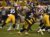 Holding out Pittsburgh Steelers running back Le'Veon Bell carries the ball against the New England Patriots