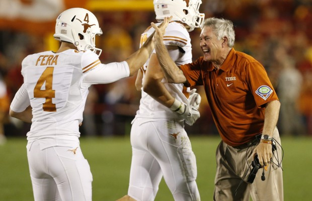 Former Texas Longhorns head coach Mack Brown celebrates with kicker Anthony Fera after he made an extra point against the Iowa State Cyclones