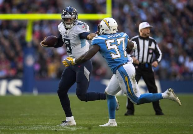 Tennessee Titans quarterback Marcus Mariota holds off Los Angeles Chargers' Jatavis Brown