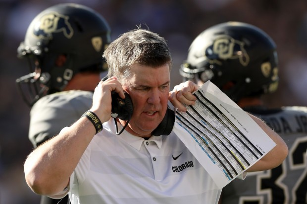 Colorado Buffaloes head coach Mike MacIntyre walks back to the sidelines after a break in the action