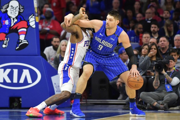 Orlando Magic forward Nikola Vucevic being defended by Philadelphia 76ers' Amir Johnson